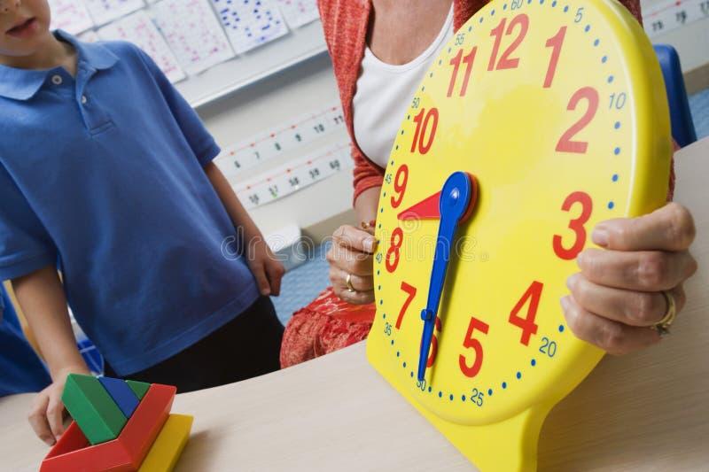 Учитель демонстрируя время к детям стоковые изображения rf