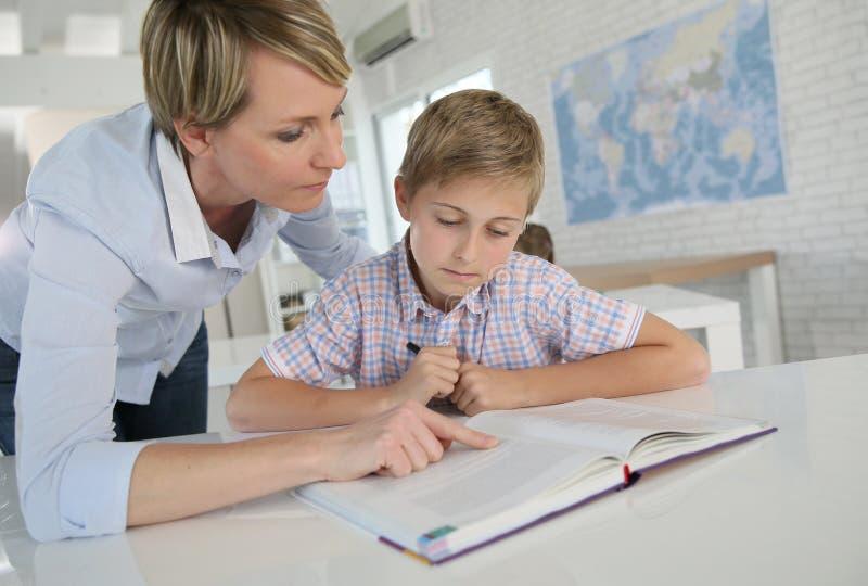 Учитель женщины помогая молодому зрачку в классе стоковые фотографии rf