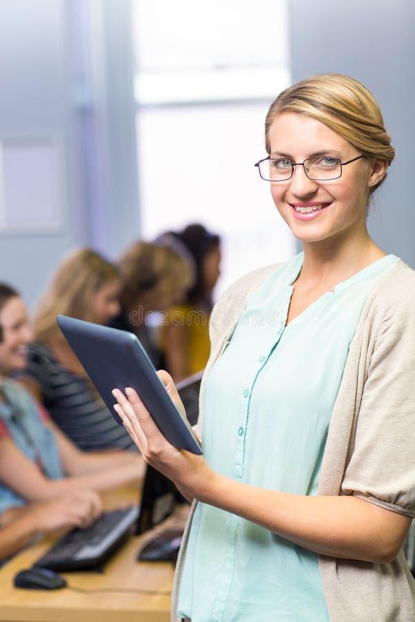 Учитель используя цифровую таблетку в классе компьютера стоковое изображение rf