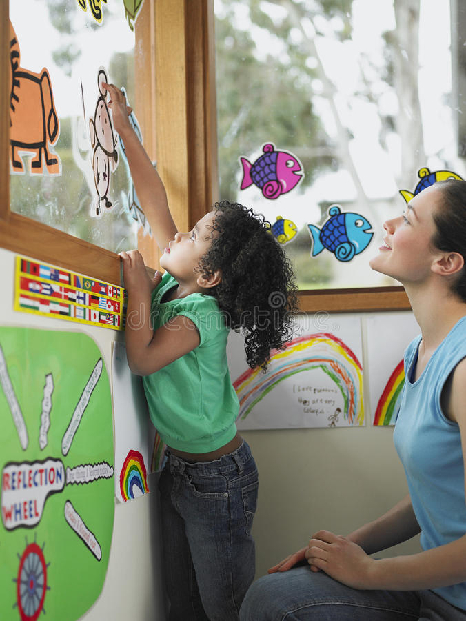 Учитель и девушка украшая окно с чертежами выреза стоковые фотографии rf