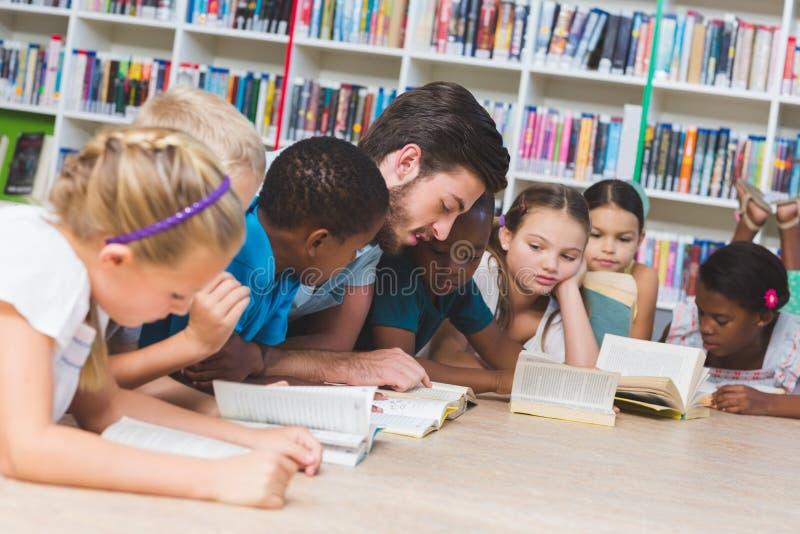 Учитель и дети лежа на книге чтения пола в библиотеке стоковые изображения