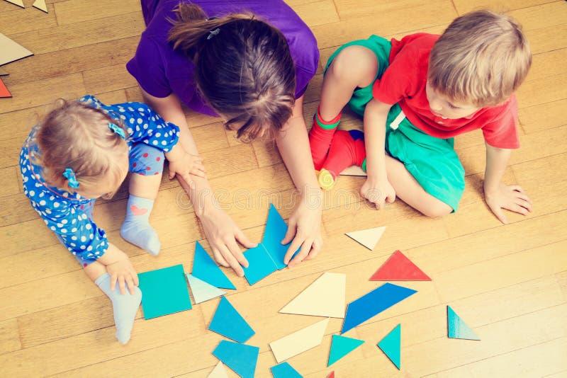 Учитель и дети играя с геометрическими формами стоковые изображения