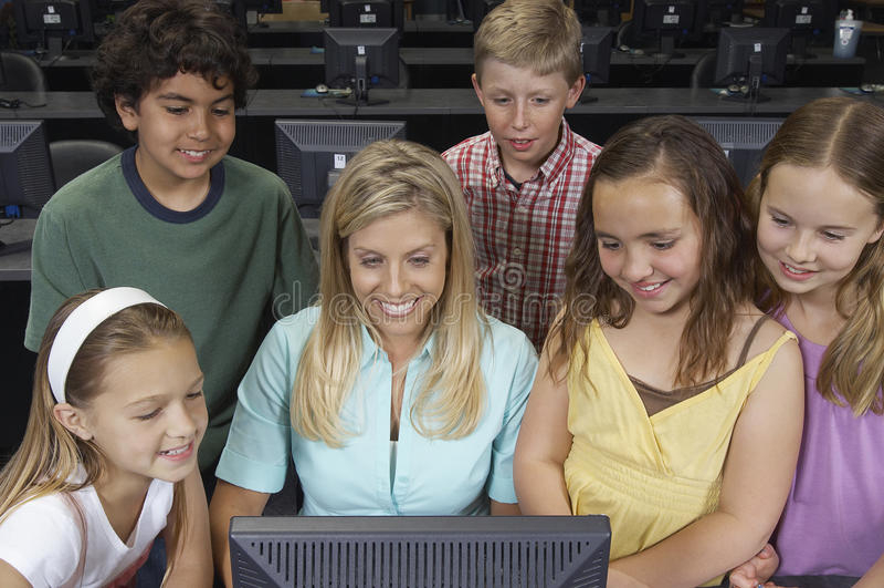 Учитель и дети используя компьютер стоковое изображение rf