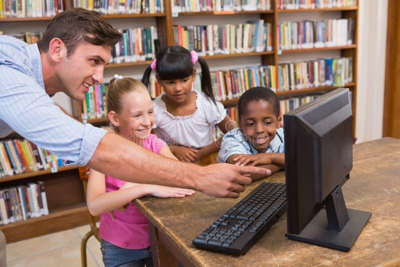 Учитель и зрачки используя компьютер на библиотеке стоковое изображение rf