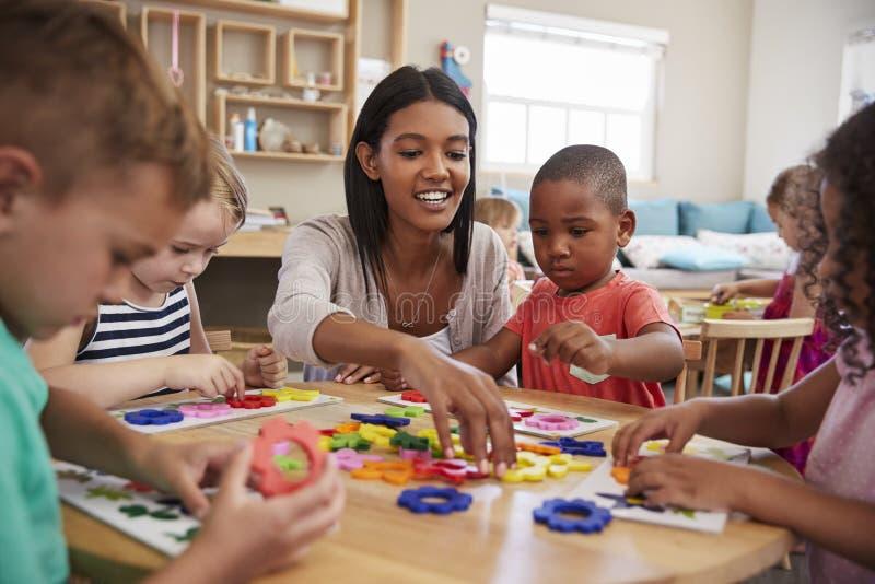 Учитель и зрачки используя формы цветка в школе Montessori стоковая фотография rf