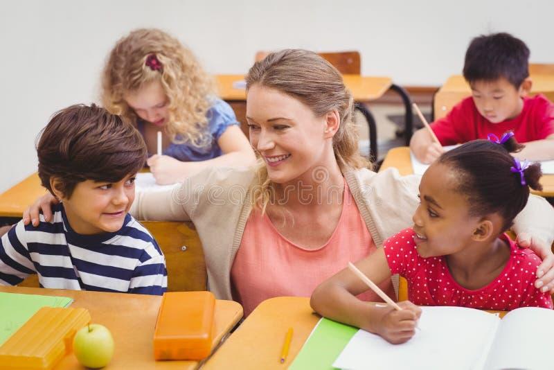 Учитель и зрачки работая на столе совместно стоковые фото