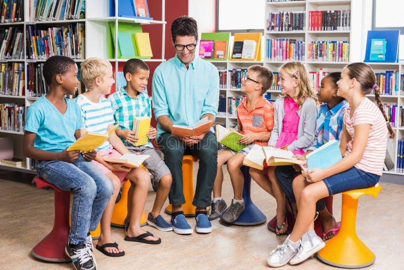 Учитель и книга чтения детей в библиотеке стоковые изображения rf