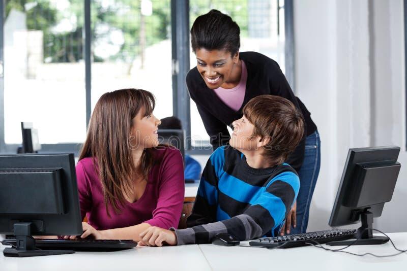 Учитель и подростковые студенты в лаборатории компьютера стоковое изображение