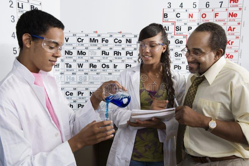 Учитель и студенты в классе науки стоковые фотографии rf
