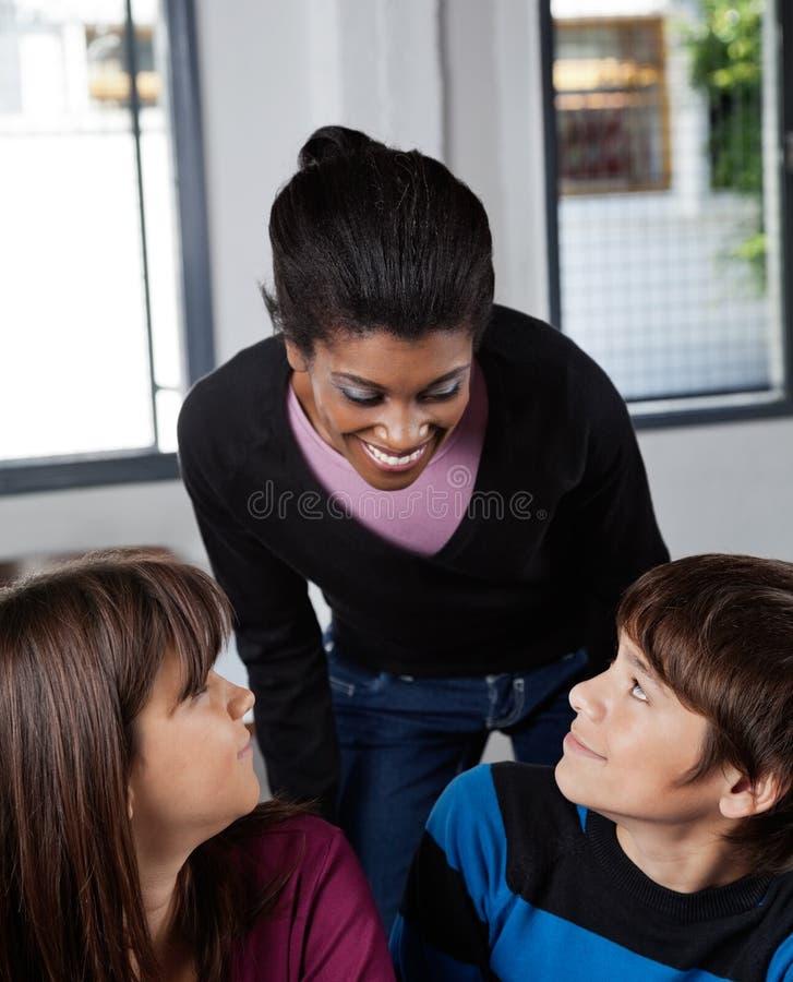 Учитель и школьники в классе стоковая фотография rf