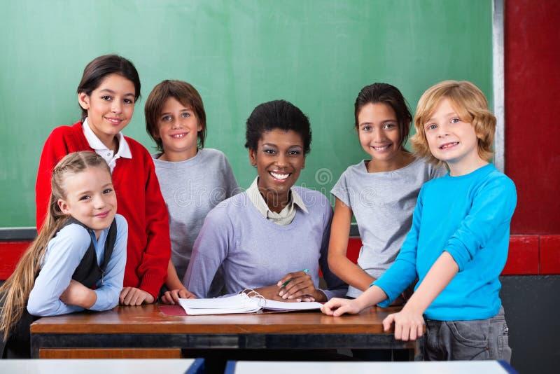 Учитель и школьники усмехаясь совместно на стоковое фото