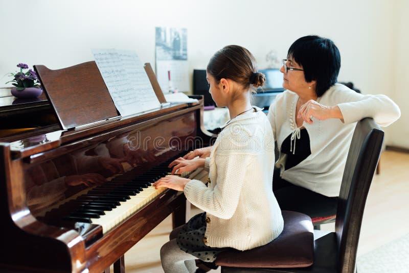 Учитель музыки с зрачком на рояле урока стоковое фото