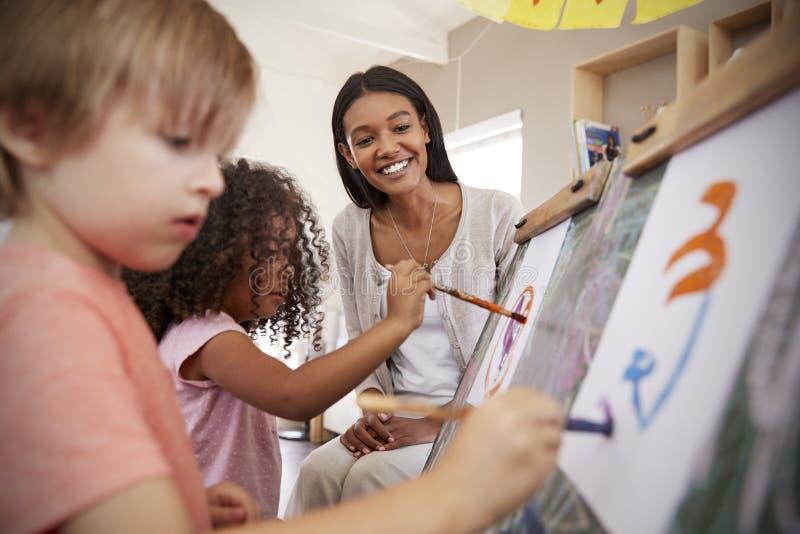 Учитель на детях порции школы Montessori в художественном классе стоковые фотографии rf