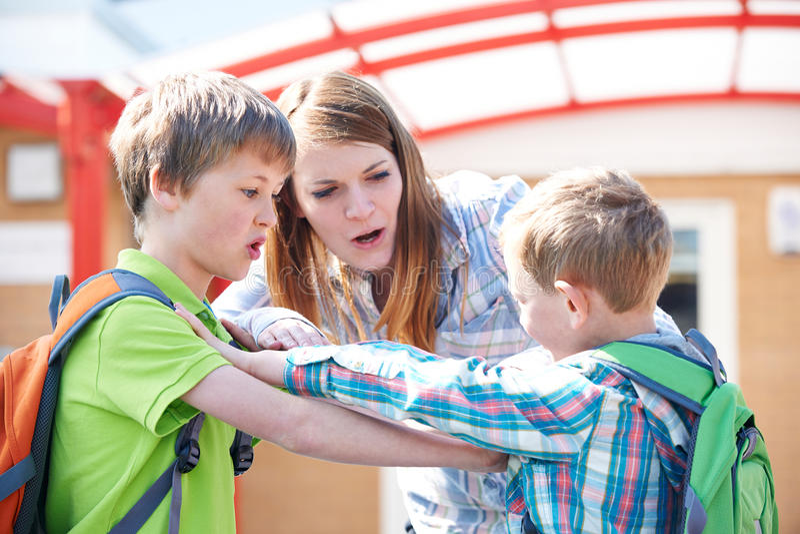 Учитель останавливая 2 мальчиков воюя в спортивной площадке стоковое изображение