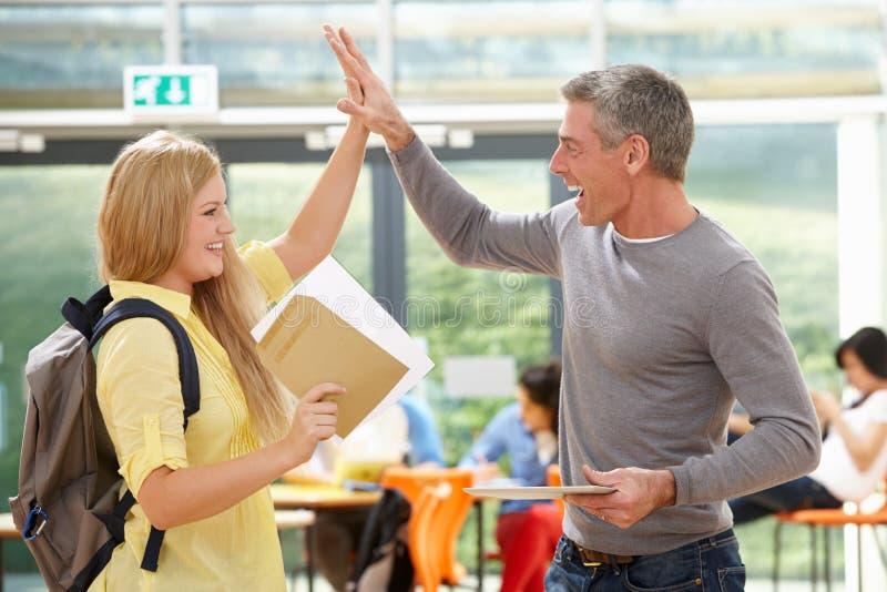 Учитель поздравляя зрачок на успешном результате экзамена стоковое изображение rf