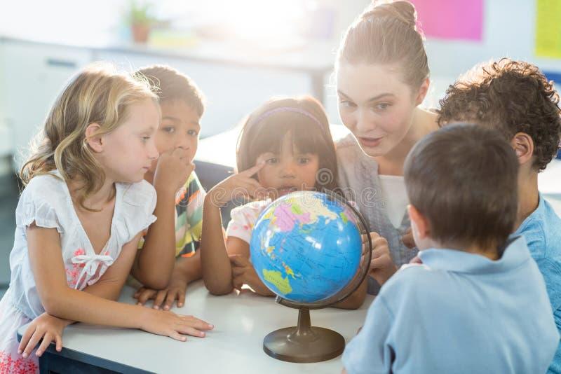 Учитель показывая глобус к школьникам стоковые фото
