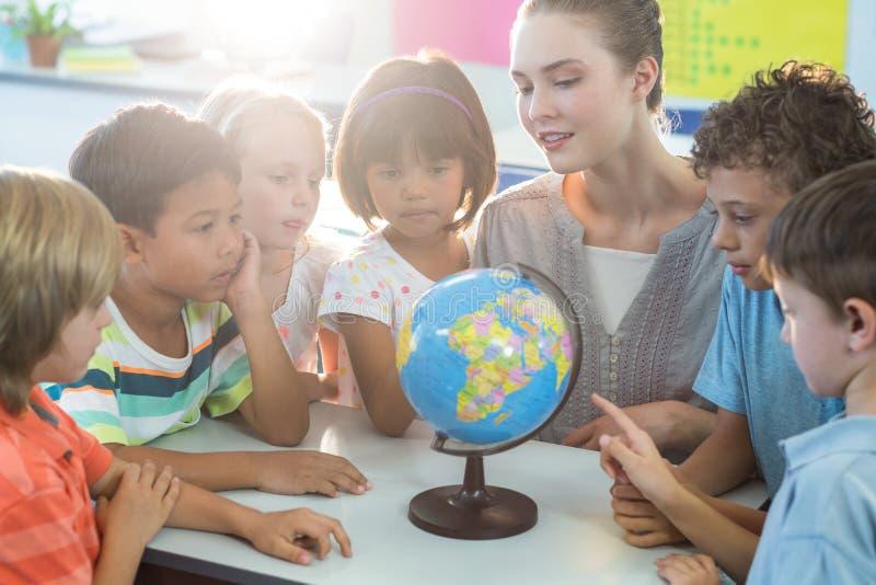 Учитель показывая глобус к школьникам стоковое изображение rf