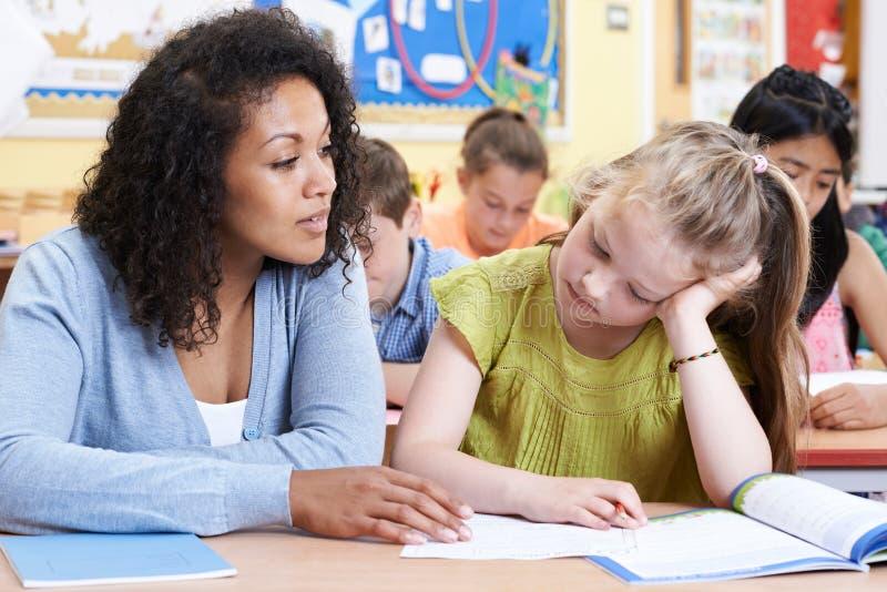Учитель помогает женскому зрачку начальной школы с проблемой стоковое фото