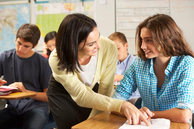 Учитель помогая женскому зрачку изучая на столе в классе стоковая фотография rf