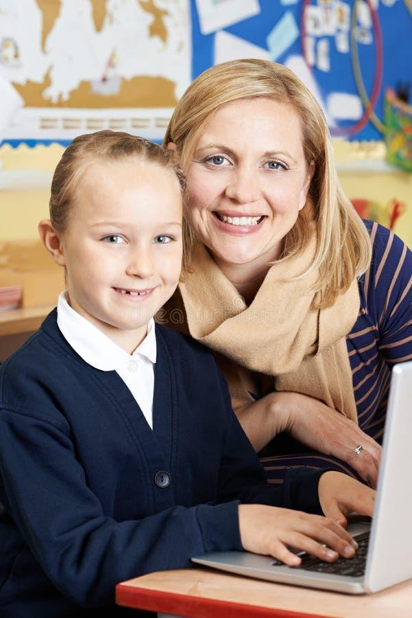 Учитель помогая женскому зрачку начальной школы в компьютере классифицировать стоковое фото rf