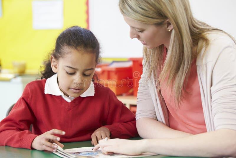 Учитель помогая женскому зрачку с практикуя читать на столе стоковые изображения rf