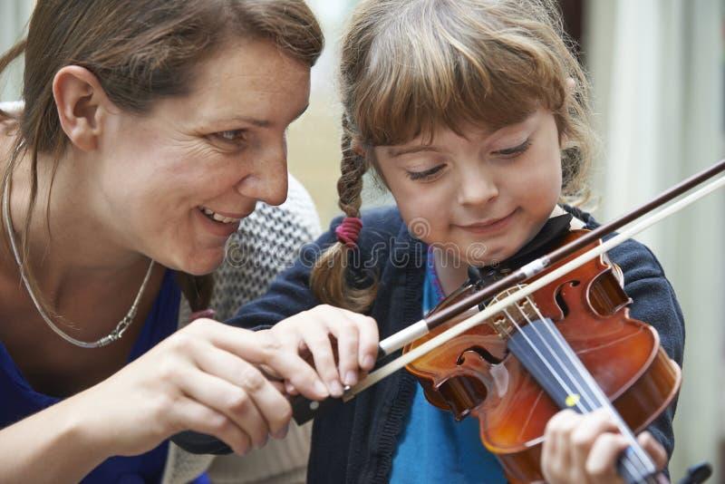 Учитель помогая молодому женскому зрачку в уроке скрипки стоковая фотография