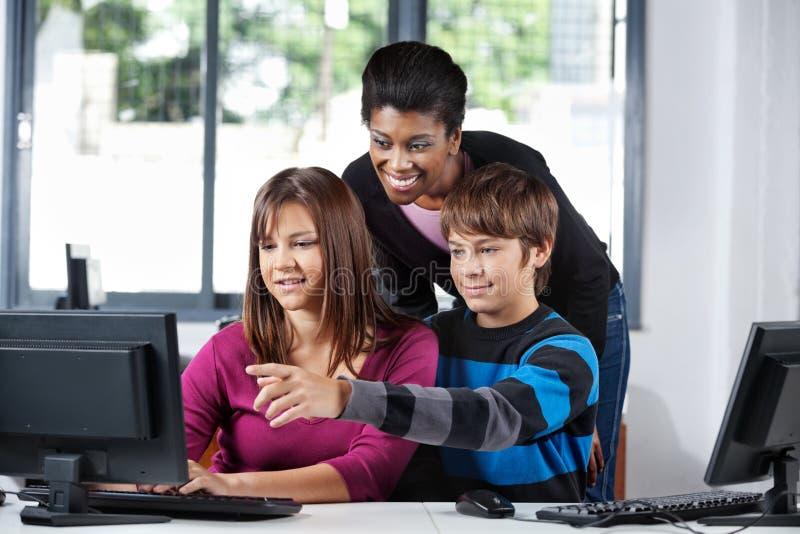 Учитель помогая подростковым студентам в лаборатории компьютера стоковое фото rf