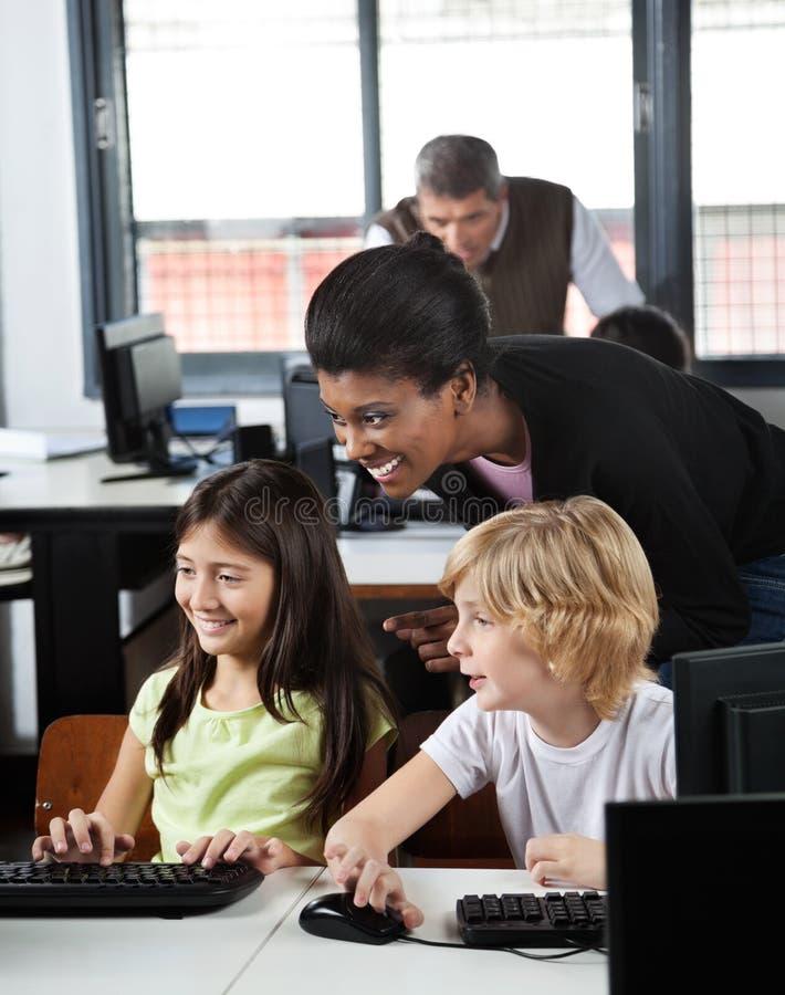 Учитель помогая школьникам в использовании настольного компьютера стоковые фотографии rf