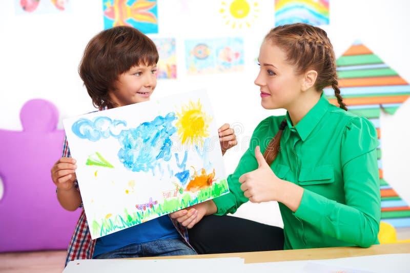 Учитель при большой палец руки вверх смотря чертеж мальчика стоковые изображения