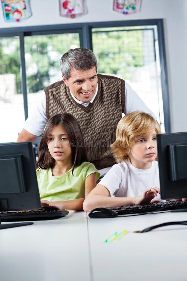 Учитель смотря школьников используя настольный ПК стоковые изображения rf