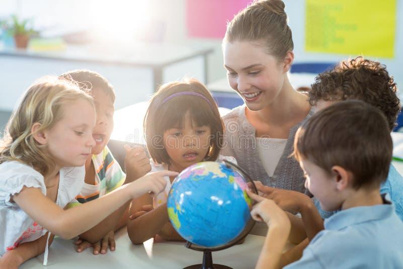 Учитель смотря школьников касаясь глобусу стоковая фотография