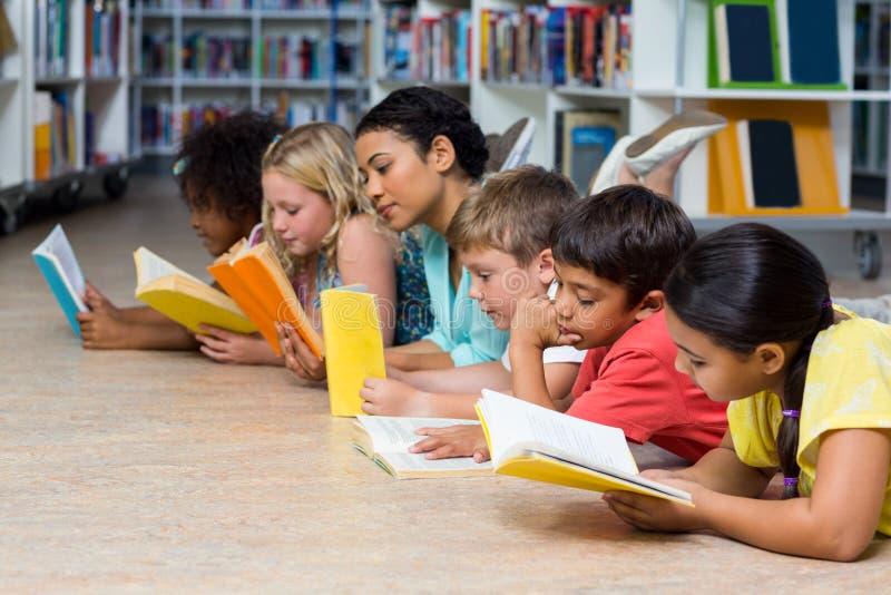 Учитель с книгами чтения студентов пока лежащ вниз стоковые фотографии rf