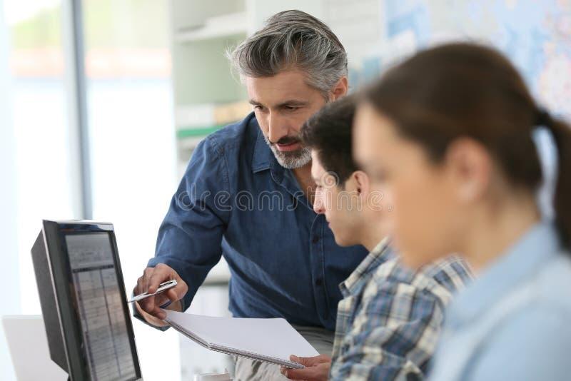Учитель с молодые люди в классе стоковая фотография rf