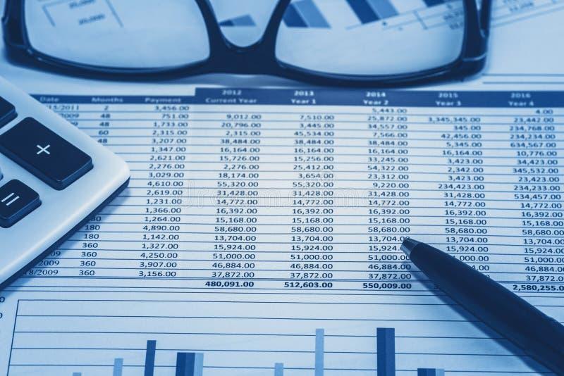 Учитывая финансовые данные по электронной таблицы запаса счета в банке банка для бухгалтера с ручкой стекел и калькулятора в голу стоковое фото rf