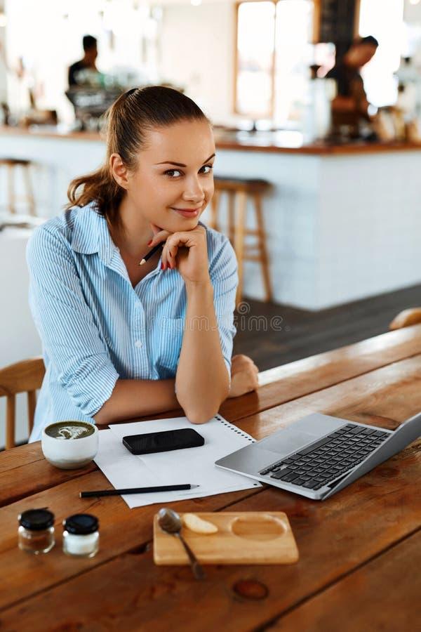 Учить, изучающ Женщина используя портативный компьютер на кафе, работая стоковое фото
