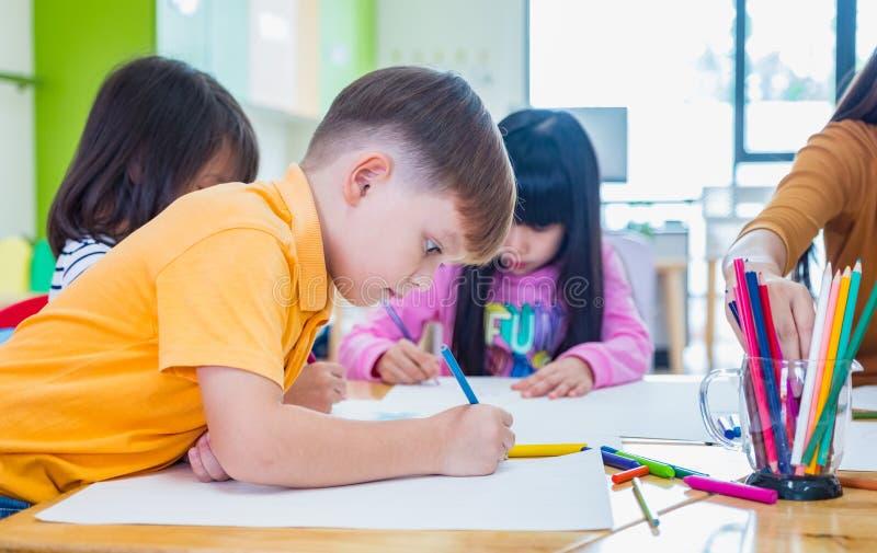 Учить кавказского ребенк этничности мальчика усмехаясь белый в классе с друзьями и учителем в школе детского сада, образовании стоковые фото