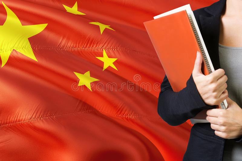 Учить концепцию китайского языка Положение молодой женщины с флагом Китая на заднем плане Учитель держа книги, оранжевый пробел стоковое изображение