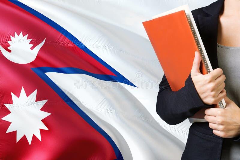 Учить непальскую концепцию языка Положение молодой женщины с флагом Непала на заднем плане Учитель держа книги, апельсин стоковые изображения