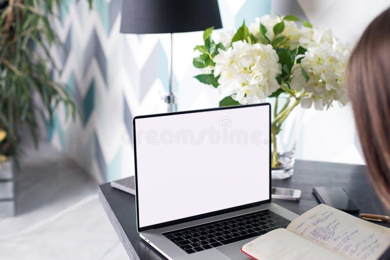 Учить студента университета женщины онлайн используя учебник и портативную сет-книгу с насмешкой вверх по пустому экрану с космос стоковое фото