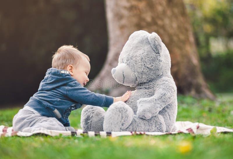 лучшие друг Милый малыш играя outdoors с его плюшевым медвежонком стоковые фото