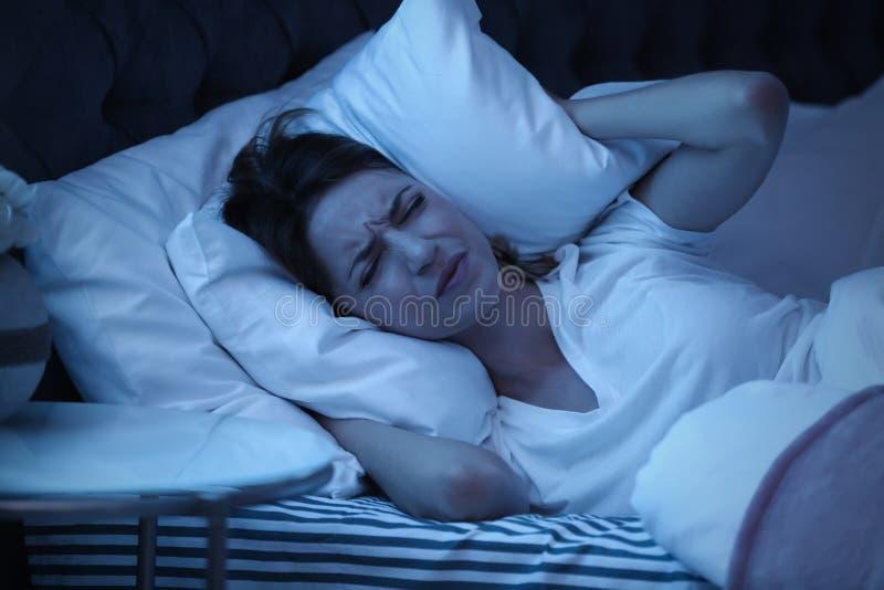 Уши заволакивания молодой женщины с подушкой пока пробующ для того чтобы спать в кровати стоковая фотография rf
