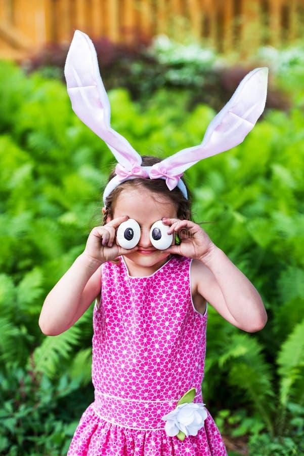 Уши зайчика маленькой девочки нося и придурковатые глаза яичка стоковое фото