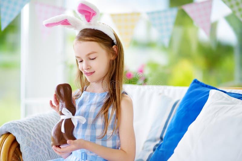 Уши зайчика милой маленькой девочки нося есть кролика пасхи шоколада Ребенк играя охоту яичка на пасхе стоковое фото rf
