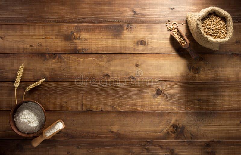 Уши и пшеничная мука на древесине стоковые изображения rf