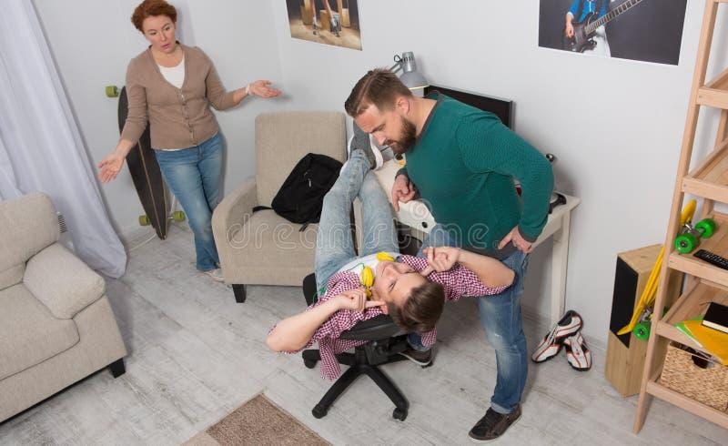 Уши подростка заключительные пока родители споря с ним стоковая фотография