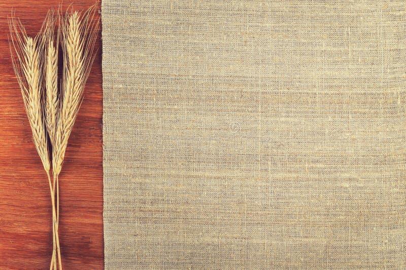 Уши пшеницы и linen ткани на деревянном взгляд сверху предпосылки стоковое фото rf