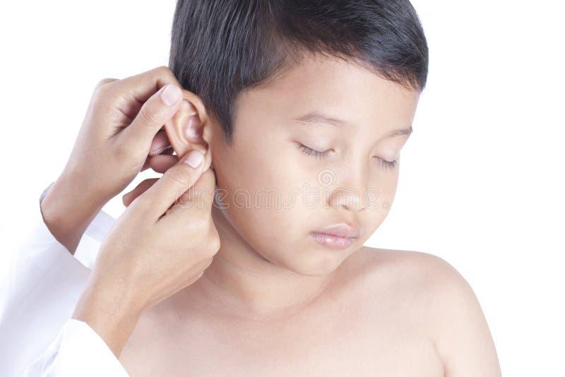 Уши ` s мальчика доктора рассматривая стоковое изображение