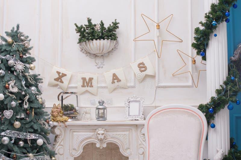 Уютная живущая комната освещенная с многочисленными светами украсила готовое для того чтобы отпраздновать рождество Дизайн интерь стоковое фото