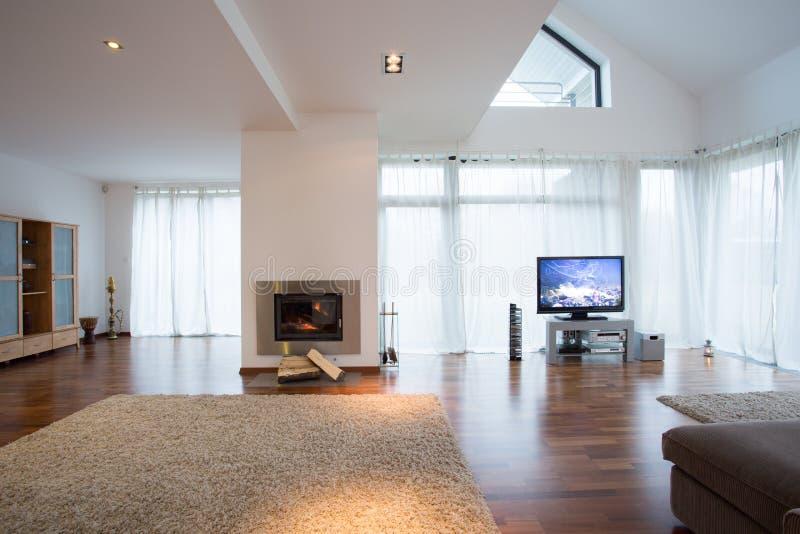 Уютная живущая комната с большими окнами и камином стоковые изображения rf