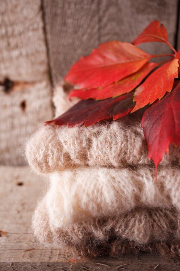 Уютная и мягкая теплая предпосылка падения осени, связанный свитер и листья красного цвета на старой винтажной деревянной доске П стоковая фотография rf